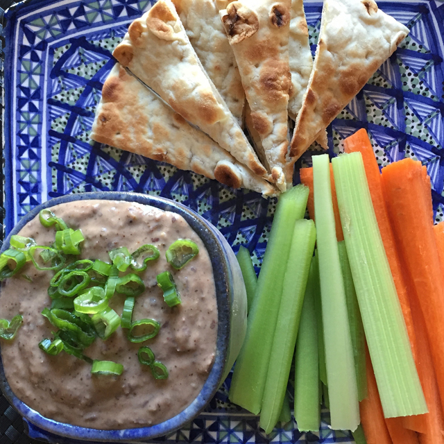 Carrots and pita on a plate with a bowl of black bean dip.