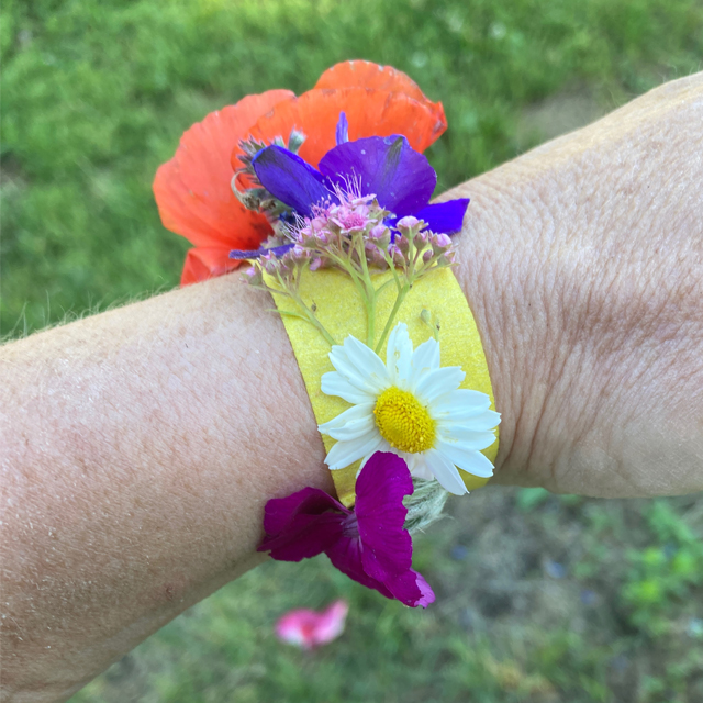 Wrist with tape and flowers stuck on the tape.