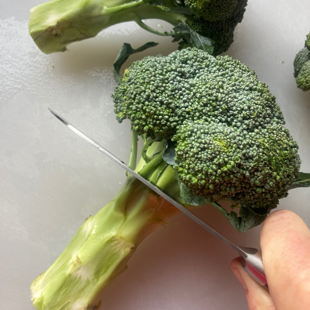 Cutting the stalk off broccoli with a knife.