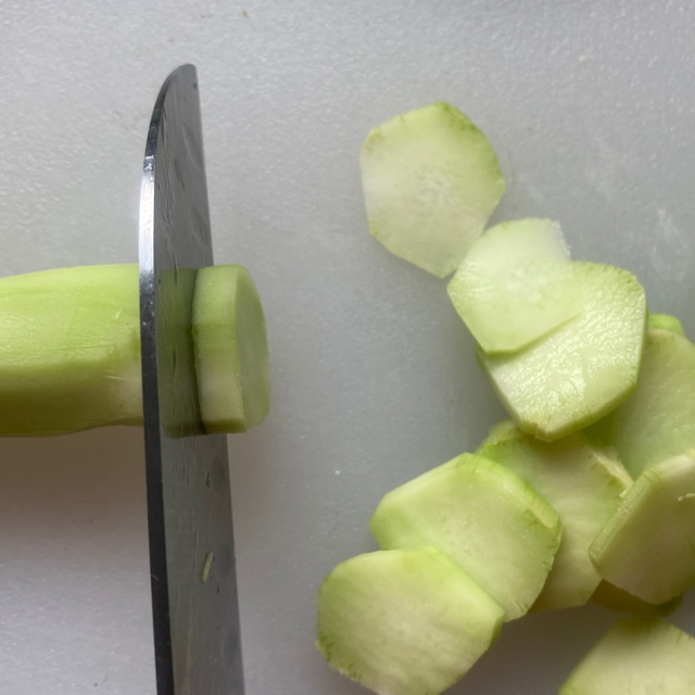 Cutting the broccoli stalk into thin coins.