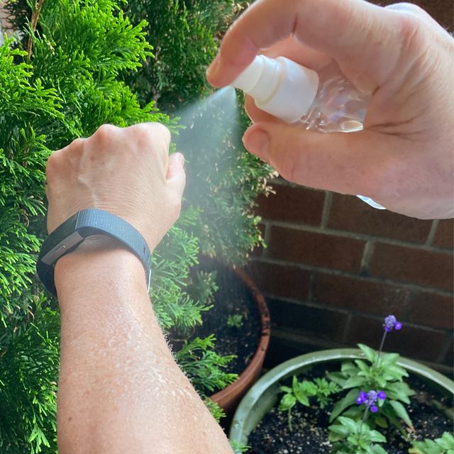 Bug repellent being sprayed onto an arm.