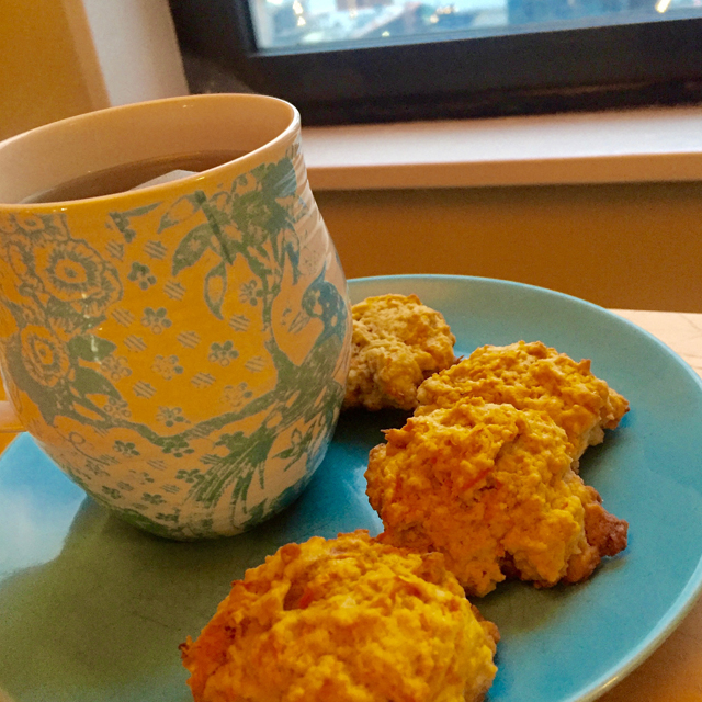 finished carrot cookies on a plate with a cup of tea