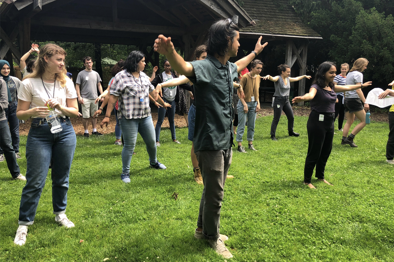 Adults standing in loose rows on a lawn, playing the compost shuffle game.