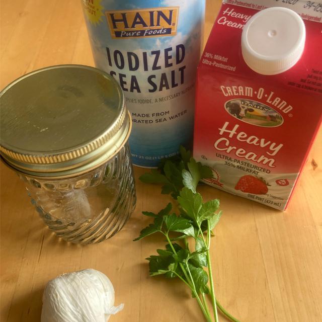 Jar, cream, salt, garlic, and herbs on a table.