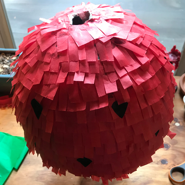 Balloon being decorated with strips of tissue paper.