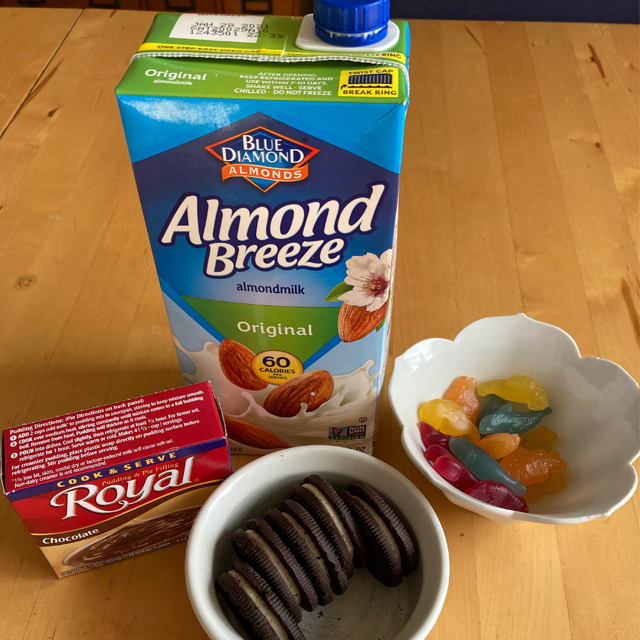 Pudding mix, cookies, almond milk, and gummy worms.