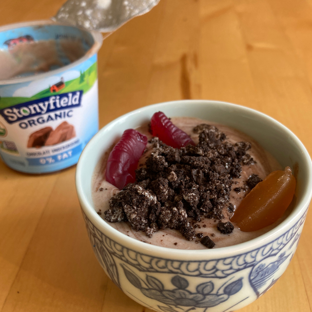 Chocolate yogurt in a bowl with gummy worms.