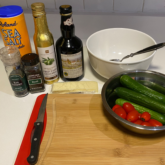 Ingredients for salad: cucumber, tomato, oil, and vinegar on a cutting board.