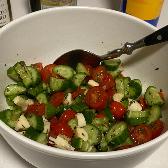 Finished cucumber and tomato salad in a bowl.