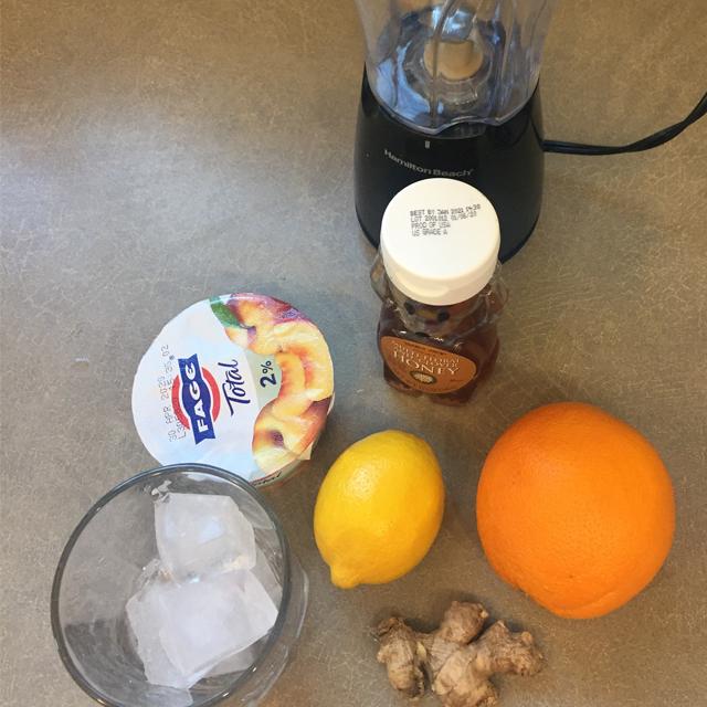 Blender, orange, lemon, ginger, ice and honey.