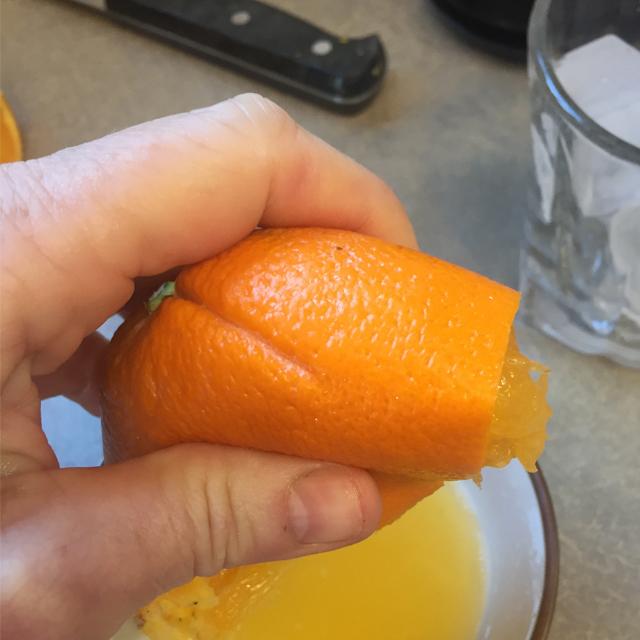 Squeezing an orange to make juice.