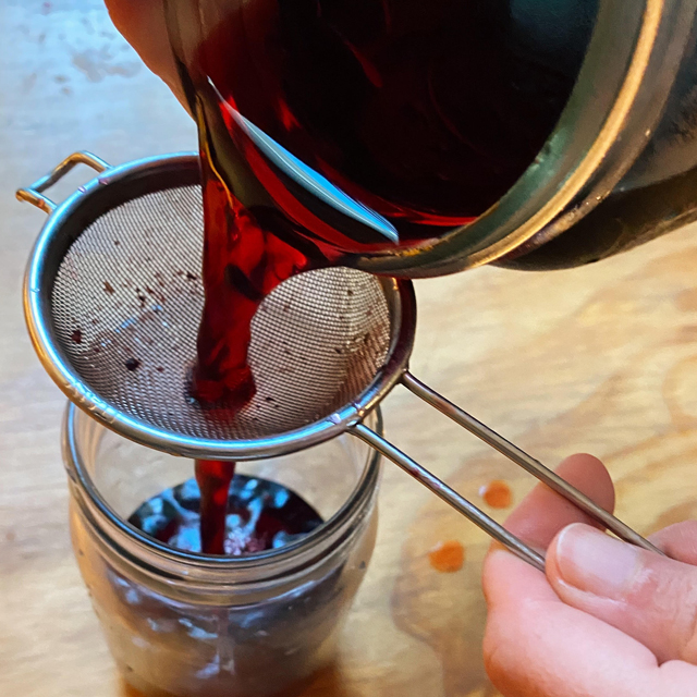 Straining the finished sorrel mixture into a glass jar.