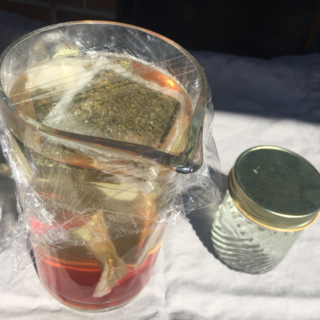 Pitcher and mason jar filled with water and tea bags sitting in the sun.