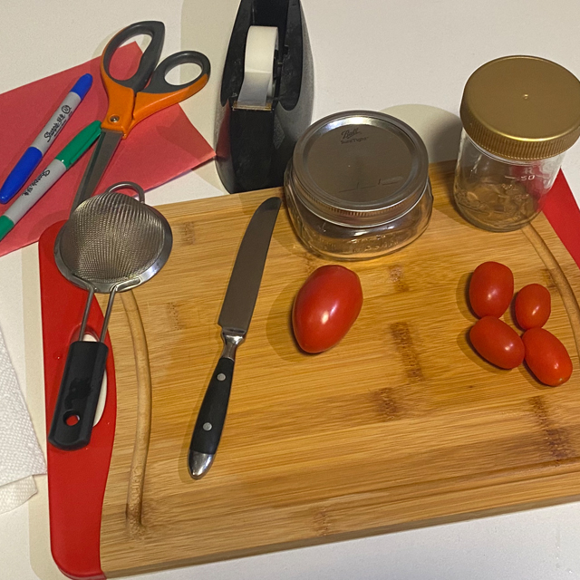 Tomato, knife, scissors, and glass containers.