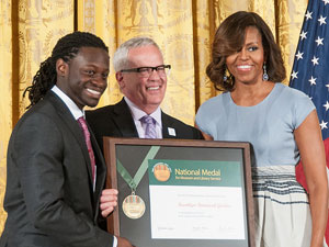 BBG President Scot Medbury and Chidi Duke, instructor and alumnus of BBG's Children's Garden, accept the 2014 National Medal for Museum and Library Service from First Lady Michelle Obama