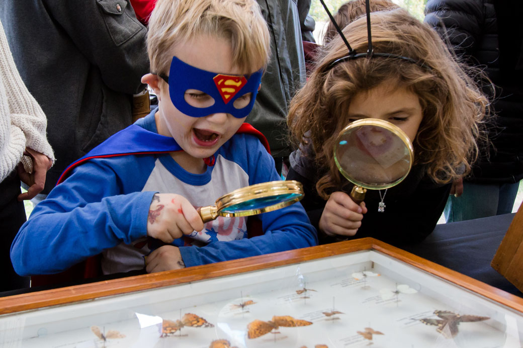 Two kids look at insects with a magnifying glass