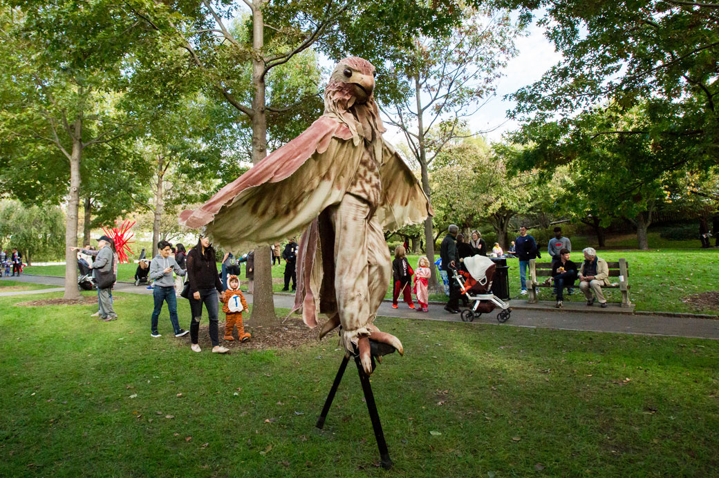 A man dressed up as an eagle walks on stilts.